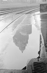 [Train tracks and a reflection of the Marine Building in the water]