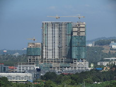 Platinum Tower (1 Sulaman) Under Construction (thienzieyung) Tags: new morning travel blue trees windows red terrain eye tower birds buildings construction apartments view zoom towers places front aerial hills cranes roofs views malaysia balconies kotakinabalu suburbs tall geography complex development forests sabah condominiums bukit ridges cladding slopes kokol sepangar thienzieyung 1sulaman platinumtower