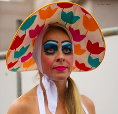 It's not an Easter Bonnet (loobyloo55) Tags: pink blue red portrait orange woman white hat female eyes sydney australia hydepark f18 mardigras 50mmlens f18ii