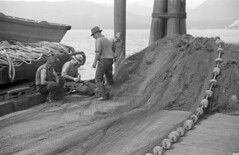 [Fishermen repairing nets on dock]