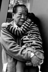 Doing the Best He Can (TheWanderingAmerican) Tags: china old sleeping blackandwhite white man black senior hongkong blackwhite holding support tears dad sad sleep father crying daughter grandfather chinese streetphotography grand grandpa elderly tired cry kowloon cries citizen hold supporting
