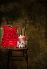A little girl's fancy red Christmas dress on a chair beside Christmas presents and ornaments (Marlene's photography) Tags: christmas decorations stilllife childhood vertical wrapping festive chair dress atmosphere nobody celebration ornaments presents fancy littlegirl atmospheric preparation baubles frilly arcangelimages marleneford