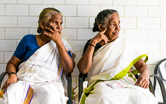 Inspect (relishedmonkey) Tags: nikon d5300 people women colour two friends look stare inspect seated outside lighting highlights day sun seats wall design saree green blue dress
