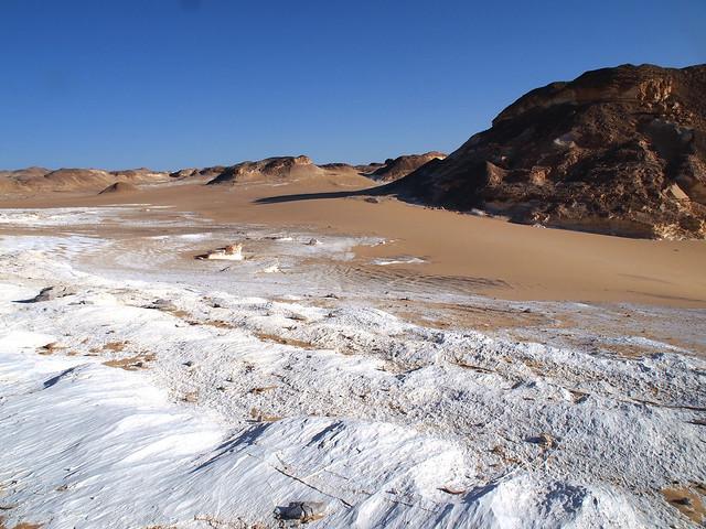 <p>星の砂漠。<br/>白い岩盤が露出し、その上を明るい色の砂が波のように覆っている。</p>