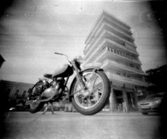 1940 Motorbike (Salt.as) Tags: city bw white black building vintage square 1940 pinhole greece motorbike homemade crop plus 50 scape ilford 9mm patras panf plateia georgiou