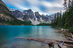 quiet night on the lake (john dusseault) Tags: morainelake water longexposure logs driftwood mountains rockies canada alberta sky clouds