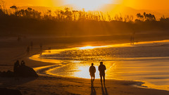 Taking a walk in the sunlight shower (Masa_N) Tags: byronbay trees beach winter peoplesilhouette water australia sunlight sand gold glitter evening seashore sea newsouthwales  au