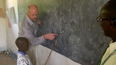 The Gambia: Teacher Helps Student Learn Letters