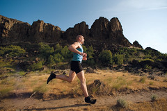 Ultrarunner shot at low angle, cliffs in background (Vibram China) Tags: statepark usa oregon training washington rocks unitedstates running run cliffs crosscountry countries pacificnorthwest states bluffs athlete distance thedalles columbiarivergorge lowangle trailrunning goldengrass ultrarunner worldlocation vibramfivefingers horesthiefbutte barefoottedmcdonald