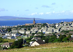 Kirkwall From The South (orquil) Tags: kirkwall town royalburgh lookingnorth view north old stmagnuscathedral spire steeple houses buildings seaside background kirkwallbay blue sea distant northisles sunny august summer sunshine orkney islands scotland uk unitedkingdom greatbritain orcades attractive interesting scenic colourful ship ferry