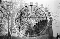 Orange Ferris wheel (biganskiy) Tags: trees orange blackwhite doubleexposure lviv ferriswheel agfa100 nikonfm greybuilding