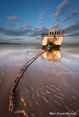 As the Sun Goes Down (Rob Grainger) Tags: light sunset sea sky seascape reflection beach clouds boat twilight fishing sand nikon rope filter lee catamaran mooring f28 beachscape 1424mm sw150