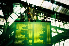 platform alteration (fotobes) Tags: people london lca xpro bokeh doubleexposure crossprocess lookingup waterloo walkway trainstation londonunderground eaves commuters waterloostation kodakelitechrome100 ratseyeview departuresboard chinscraper