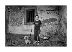 The boy and his dog (Jan Dobrovsky) Tags: bw boy contrast countrylife countryside document dog grain gypsies indoor krasnalipa leicaq portrait roma rural village