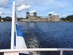 Olavinlinna castle viewed from a ship (KaarinaT) Tags: lake finnishflag olavinlinna savonlinna suomi finland cloudy water fortress stronghold old historical rockcastle castleonanisland flag