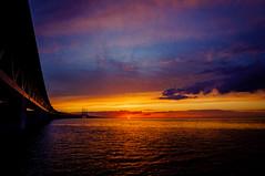 Dark bridge at sunset (Fredde Nilsson) Tags: bridge sunset sky orange sun water clouds dark denmark day purple cloudy sweden structure setting malm resund resundbridge sknecounty