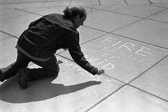 Fire Cap Police Chief (BlueRobot) Tags: film wisconsin chalk protest streetphotography 400tx madison rodinal kodaktrix400 photochallenge11picturesofstrangers