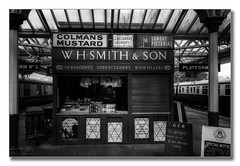 WH Smith and son (Descended from Ding the Devil) Tags: bw greatcentralrailway heritage loughborough sonya7mkii sonyalphadslr whsmith blackandwhite fullframe mirrorless monochrome newsagent photoborder platform station steam