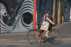 Female Cyclist, Hilton Street, Northern Quarter, Manchester, England. (westport 1946) Tags: england unitedkingdom manchester manchesterstreets streetphotography stevensonsquare hiltonstreet streetart streetview streetscene urbanart urbanscene muralart murals shopfronts shoppingstreet shuttermural shutters graffiti femalecyclist female cycle cykler cyclist bike bicicletas bicycle biciclette bicicletta cyclehelmet sidewalk pavement outdoor cornerbarbershop barbershop orangecycle orangebike oklahoma bag