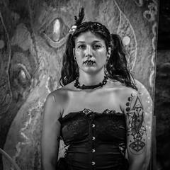 Street Portrait (tim.perdue) Tags: street portrait girl woman person figure candid stare black white bw monochrome costume makeup tattoo mural background performer face goth dark alternative tribal voodoo