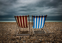 Weather The Storm Together by Simon & His Camera (Simon & His Camera) Tags: weather cloud sky horizon chair red blue deckchair clouds beach stones water sea coast colours landscape outdoor simonandhiscamera skyline waterfront