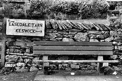 Somewhere to sit ! (CJS*64) Tags: nikon nikkorlens nikkor nikond7000 dslr d7000 18mm105mmlens cumbria thelakes beauty dayout cjs64 craigsunter cjs countryside grasmere blackwhite whiteblack whiteandblack bw mono monochrome seat sign bench sit wood wall