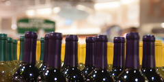 Wine bottles shot with limited depth of field on display in a liquor store (DigiDreamGrafix.com) Tags: old red white dusty industry glass yellow drunk vintage store vineyard bottle industrial factory tour flavor purple wine quality background fine beverage basement cyan vine row tourists storage line winery alcohol production taste merlot alcoholic dust product arrangement cellar gree corks vino winemaking bottling ferment intoxicant