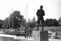 walk on by (bergytone) Tags: analog film bw canon 110 110ed ilford fp4 xtol oneten grandhaven mi boardwalk statue