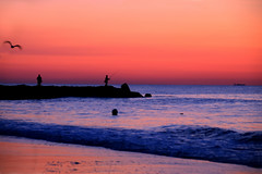 Sunrise at Ocean Grove (Moniza*) Tags: ocean sunset sea sky seascape reflection beach nature water silhouette club clouds sunrise landscape dawn pier newjersey twilight fishing sand nikon rocks waves nj rocky explore shore jersey bluehour jerseyshore oceangrove d90 explored moniza