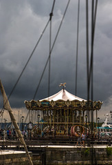 the storm is coming but the carousel (merry-go-round) spins, Honfleur, Normandy, France (grumpybaldprof) Tags: vieuxbassin oldharbour honfleur normandie normandy france quaistecatherine quaiquarantaine quai quaistetienne stecatherine lalieutenance quarantaine water boats sails ships harbour historic old ancient monument picturesque restaurants bars town port colour lights reflection architecture buildings mooring sailing stone collombage halftimbered yachts carousel merrygoround building details colours contrast architectural textures bricks age features wandering streets doors wood timber slate halftimbered oak plaster traditional norman hdr storm clouds people walking mobilephones tamron 16300 16300mm tamron16300mmf3563diiivcpzdb016 ropes rigging depthoffield foreshorten perpsective