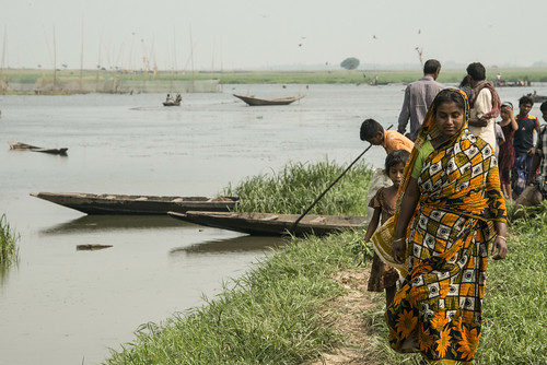 A lady walking by a river in Sunamganj, Bangladesh. Photo by Finn Thilsted, 2013.