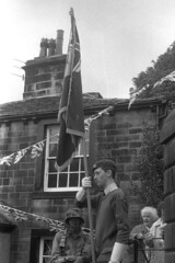 Standard Bearer (Julian Dyer) Tags: vintage blackwhite events yorkshire 35mmfilm ilforddelta400 fujicast705 haworth ilfordddx haworth1940sweekend haworth1940s
