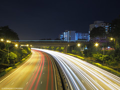 Cars along the KJE (Kranji Expressway) with a SMRT train crossing, Singapore (monique_sg) Tags: highway night singapore olympus epm2 slow panasonic lumix 20mm panasonic20mmf17 slowshutter nightphotography freeway road