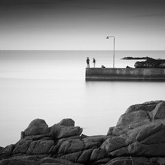 Watching the Day Fade Away (panfot_O (Bernd Walz)) Tags: sea seascape water waterscape harbor marina pier rocks evening coast shore bornholm blackandwhite bw monochrome square fineart contemplation silence calm peaceful atmosphere mood longexposure