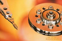 Hard Disk Drive (William Christensen) Tags: red orange macro reflection metal colorful technology metallic platter harddiskdrive macromonday willchristensen nikonmicronikkor200mmf4
