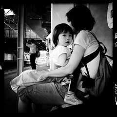 in her arms (librarymook) Tags: street blackandwhite bw woman station japan train square child candid mother noflash chiba squareformat commuter sakura commuting mobilephotography johnslens iphoneography hipstamatic aodlxfilm