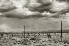 breaking II (bytegirl24) Tags: bw storm newmexico santafe field clouds fence barbedwire barbwire hff happyfencefriday