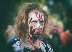 A Zombie Aftermath (henriksundholm.com) Tags: zombie zombiewalk vignette piercing portrait people man guy face blood gore horror terror wounds wounded shirt dof bokeh 50mm sdermalm fatbursparken park medis medborgarplatsen eyes hair lips mouth teeth throat head livingdead makeup shadows dark parade stockholm sverige sweden female girl woman lady