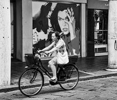 Mantua 02 (Peter.Bartlett) Tags: billboard bag noiretblanc shopfront postergirl people city urbanarte bike peterbartlett urban woman candid streetphotography m43 microfourthirds cycle bw shopwindow macphuntonality lunaphoto poster olympusomdem1 mantova lombardia italy it blur speed motion