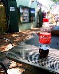 Pop Culture (Chris C. Crowley) Tags: popculture coke cocacola pop soda drink bottle resting table shadows light flag street shops staugustineflorida
