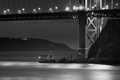 The Little House Under The Bridge...... (M. Shaw) Tags: ocean sanfrancisco california longexposure bridge sea blackandwhite bw cliff lighthouse building history beach fog night clouds lights historic goldengatebridge bayarea sausalito 100400mm californiacoast sheetmetal cloudynight ef100400mmf4556lisusm mshaw silverefexpro 5dmark2 canoneos5dmarkll silverefexpro2
