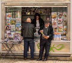 'Biblioteca' (Canadapt) Tags: magazines news kiosk woman merchant men reading street alfama lisbon portugal canadapt
