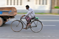 Sri Lanka sarong (jeremyhughes) Tags: road street motion bike bicycle speed cycling movement nikon cyclist sandals sigma riding srilanka panning rider sarong traditionaldress nikond700