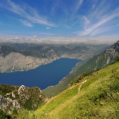 Stunning backdrop of Lake Garda's mountainous Northern Shore (Bn) Tags: camera blue summer sky italy panorama mountain lake holiday alps smile car cheese trekking garden walking polaroid milk italian topf50 garda rocks europe strada mediterranean italia photographer view cows hiking path altitude cable primo panoramica paragliding elevated peaks paraglider viewpoint fiore higher topf100 walkers mont climate breathtaking malcesine paragliders gardameer baldo 100faves 50faves panview 2218m