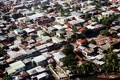 33-603 (ndpa / s. lundeen, archivist) Tags: nick dewolf nickdewolf 33 reel33 color photographbynickdewolf 1970s 1972 fall film 35mm winter 1973 aerial fromtheair fromtheairplanewindow unidentified buildings houses homes roofs rooftops