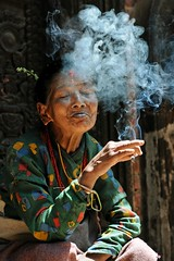 Old woman smoking in front of a temple, Bhaktapur (Npal) ([cation]) Tags: voyage viaje travel cation gatherer cueilleuse plantation woman mujer femme portrait retrato 50mm collier collar agriculture nikon d300 temple templo bhaktapur kathmandou kathmandu npal nepal smoke smoking humo fume tradicion traditionnal traditionnel tranquilo light luz lumire mditation meditation meditacion bijoux bracelet sacred sacr magic magique himalaya