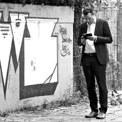 UPSIDE DOWN FOR LIFE... (Akbar Simonse) Tags: dscn3511 denhaag thehague agga haag sgravenhage lahaye holland netherlands nederland people candid man smartphone mobilephone graffiti streetphotography straatfotografie zwartwit bw blancoynegro bn monochrome vierkant square akbarsimonse upsidedownforlife