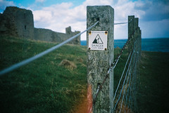 Cliff Edge (teotwawki) Tags: cliff film sign danger fence northumberland agfa cosinacx2 agfaultra100 dunstanburgh 2013
