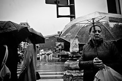 Fearing What May Come (stimpsonjake) Tags: nikoncoolpixa 185mm streetphotography bucharest romania city candid blackandwhite bw monochrome woman rain umbrella sad face
