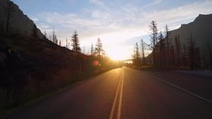 Chasing the Sun (GrisParr) Tags: glaciernationalpark montana usa midwest travel dawn road drive pavement light trees sun sunrise landscape nature beauty mountains parks sunflare sunrays outdoors sky alone ecosystem